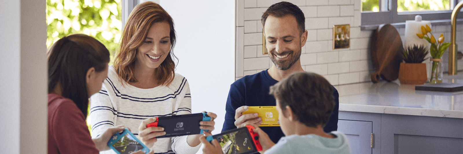 Family playing Nintendo Switch consoles together